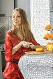 金发碧眼的女人在现代厨房切桔子 免版税图库摄影
