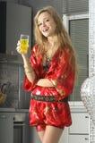 金发碧眼的女人在现代厨房里用汁液 库存照片
