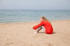 金发碧眼的女人坐一个沙滩和看海 库存图片