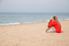 金发碧眼的女人坐一个沙滩和看海 免版税库存照片
