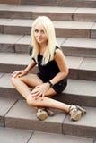 金发碧眼的女人坐台阶 免版税库存图片