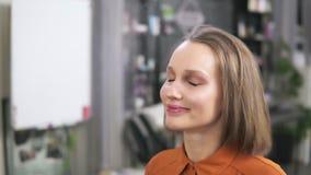 金发碧眼的女人坐椅子,并且制造艺术家fihishing她的与面孔浪花的脸 她做已经是 股票视频