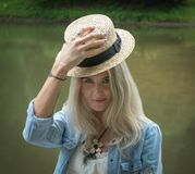 金发碧眼的女人拿着在她的手上的一个草帽并且对在一件白色礼服和一件蓝色牛仔布衬衣的照相机微笑着 关闭 库存照片
