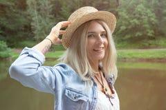 金发碧眼的女人拿着在她的手上的一个草帽并且站立在一件白色礼服和一件蓝色牛仔布衬衣的一个石码头边缘 免版税库存图片