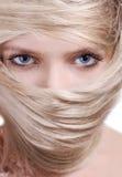 金发碧眼的女人接近的头发屏蔽时髦&# 免版税库存图片