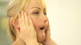 金发碧眼的女人握她的手对她的面颊,张她的嘴并且延伸她的嘴唇 股票录像
