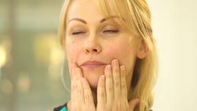 金发碧眼的女人显示定调子面孔训练,吹空气在拿着嘴用手的嘴唇下 影视素材