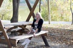 金发碧眼的女人有长凳的一基于在桌上在公园区域 库存照片