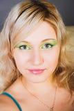 金发碧眼的女人注视绿色纵向 免版税图库摄影