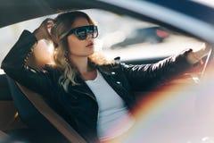 金发碧眼的女人照片在把引入汽车后的 图库摄影