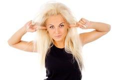 金发碧眼的女人用您的手指包括她的耳朵 库存照片