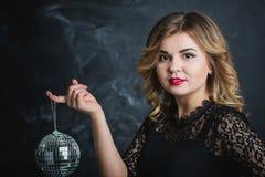 金发碧眼的女人的画象有迪斯科球的在手中 图库摄影