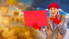 金发碧眼的女人的综合图象在冬天给拿着红色标志穿衣 图库摄影