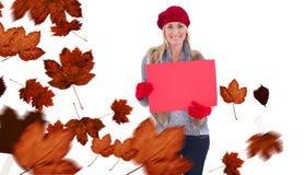 金发碧眼的女人的综合图象在冬天给拿着红色标志穿衣 库存图片