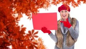 金发碧眼的女人的综合图象在冬天给拿着红色标志穿衣 免版税库存图片