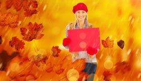 金发碧眼的女人的综合图象在冬天给拿着红色标志穿衣 库存照片