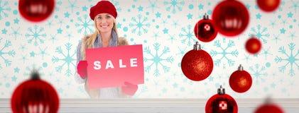 金发碧眼的女人的综合图象在冬天给拿着销售标志穿衣 免版税库存照片