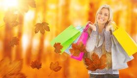 金发碧眼的女人的综合图象在冬天给拿着购物袋穿衣 免版税图库摄影