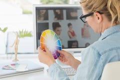 金发碧眼的女人聚焦了工作在她的书桌的设计师拿着三原色圆形图 免版税库存图片
