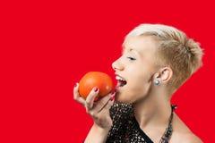 金发碧眼的女人要吃蕃茄 免版税库存照片