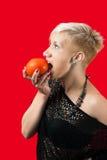 金发碧眼的女人要吃蕃茄 免版税库存图片