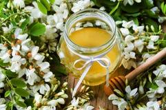 金合欢花和蜂蜜在瓶子 免版税库存照片