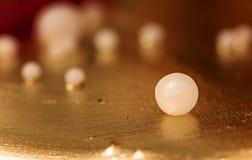 金和珍珠方旦糖蛋糕装饰品背景 库存图片