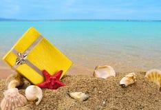 金在沙子和海的礼物盒 免版税库存照片