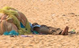 金奈,印度- 2月10 :一个未认出的人在沙子睡觉在2013年2月10日的小游艇船坞海滩附近在金奈 免版税库存图片