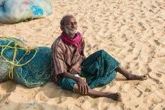 金奈,印度- 2月10 :一个未认出的人坐沙子在2013年2月10日的小游艇船坞海滩附近在金奈 免版税库存照片