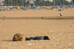 金奈,印度- 2月10 :一个未认出的年轻人在沙子睡觉在2013年2月10日的小游艇船坞海滩附近在金奈, 免版税库存图片