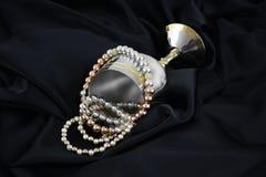 金子、在黑色丝绸的银和珍珠 免版税库存照片