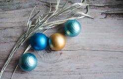 金子、绿松石和蓝色圣诞节球在木背景,装饰用一个银色分支 库存照片