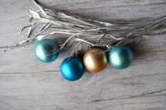 金子、绿松石和蓝色圣诞节球在木背景,装饰用一个银色分支 免版税图库摄影