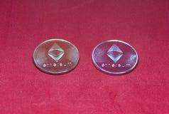 金子和银在红色背景的ethereum硬币 免版税库存照片
