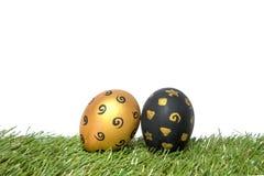 金子和黑色手工制造复活节彩蛋在绿草 库存照片