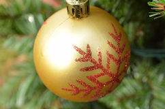 金子圣诞节与红色闪烁雪花设计的球装饰品 免版税图库摄影