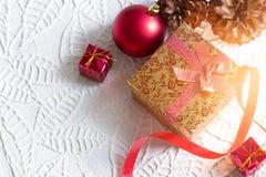 金子圣诞节在与红色中看不中用的物品的丝带栓的礼物盒在白皮书纹理 库存图片
