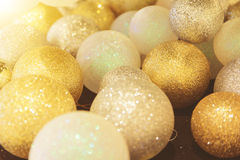 金子圣诞节球特写镜头和冷杉在与温暖的光的地板上分支 库存图片