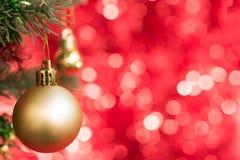 金子圣诞节球装饰品在与红色bokeh的杉树装饰 免版税库存图片