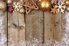 金子圣诞节装饰品与雪框架的上面边界在木头 免版税库存照片