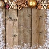 金子圣诞节装饰品与雪框架的上面边界在木头 库存照片