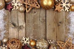金子圣诞节装饰品与雪框架的双边界在木头 免版税库存图片