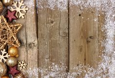 金子圣诞节装饰品与雪框架的边边界在木头 图库摄影