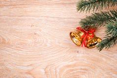 金子圣诞节铃声和杉树在土气木背景分支 看板卡例证向量xmas 新年好 顶视图 免版税库存图片