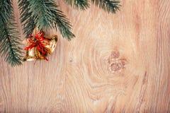 金子圣诞节铃声和杉树在土气木背景分支 看板卡例证向量xmas 新年好 免版税库存图片