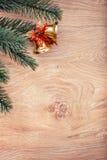 金子圣诞节铃声和杉树在土气木背景分支 看板卡例证向量xmas 新年好 免版税库存照片