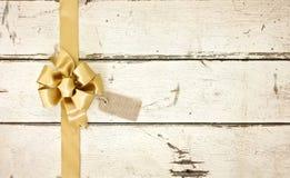 金子在玫瑰色白色的圣诞节弓困厄了木背景 免版税库存图片