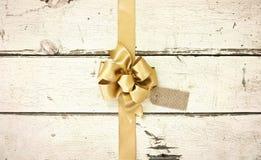 金子在玫瑰色白色的圣诞节弓困厄了木背景 图库摄影