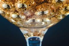 金子在酒杯成串珠状用水,泡影,宏指令,照片,设计的背景 库存照片